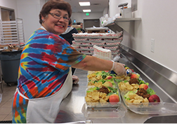 This image of a cafeteria worker preparing lunches will link to the Child Nutrition department page.