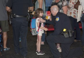 An officer helps a Cheatham student adjust her new backpack