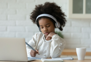 Girl with headphones works on Chromebook at kitchen table
